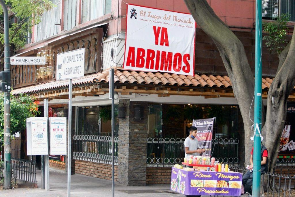 Bares y negocios colocan mantas llamativas para atraer clientes pero la gente se restringe a salir en ciertos lugares.