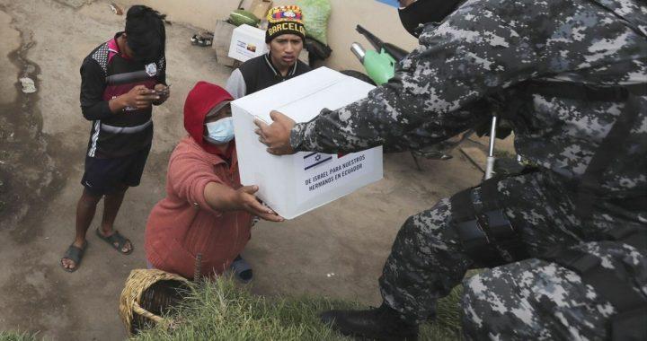 Una familia ecuatoriana recibe una despensa donada por el gobierno de Israel, a las afueras de Quito.