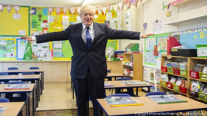 Boris Johnson opens his arms in a classroom