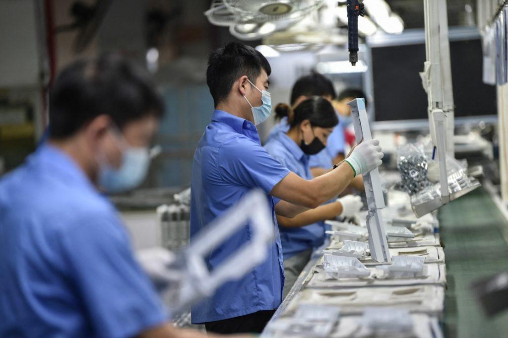 Empleados de una fábrica que produce piezas para lavadoras en la ciudad de Nankín, China.