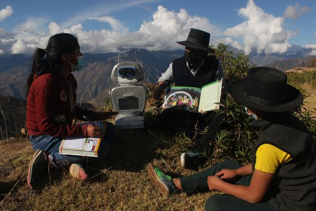Professor Walter Velasquez and two of his students attend outdoor classes with Kipi.  (Photo: Yerson Kolav)